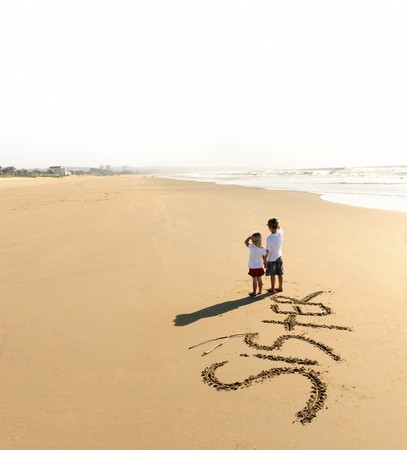 Lovely young brother and sister write words in the sand together Stock Photo - 7785544