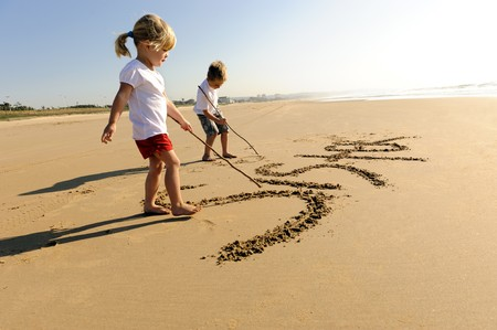 Lovely young brother and sister write words in the sand together photo