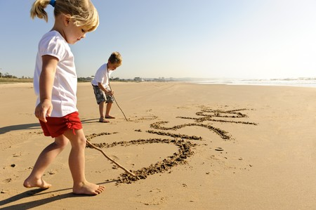 sister: Lovely young brother and sister write words in the sand together Stock Photo