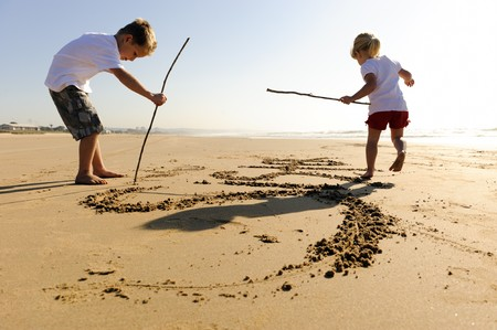 Lovely young brother and sister write words in the sand together Stock Photo - 7785564