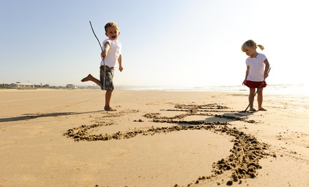 Lovely young brother and sister write words in the sand together Stock Photo - 7785556
