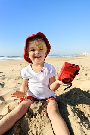 Adorable little girl takes pictures with her red camera on the beach photo