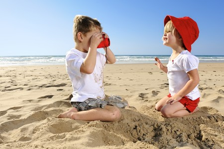 Cute young girl poses for her brother on the beach photo