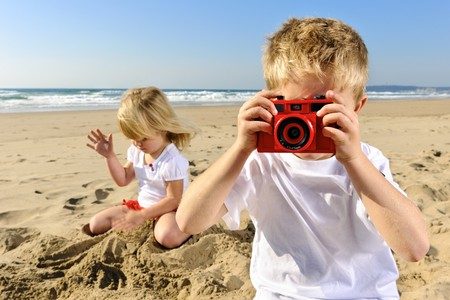 film camera: Young boy takes a picture at the beach with his red camera Stock Photo