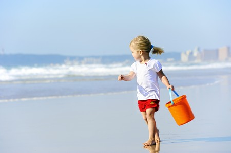 guy on beach: Brother and sister walk along the ocean edge looking for shells Stock Photo
