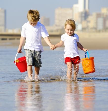 ni�os rubios: Hermano y hermana caminan al borde del oc�ano buscando conchas