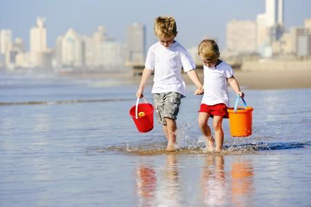 seau d eau: Fr�re et soeur marchent le long du bord de mer recherchent des obus