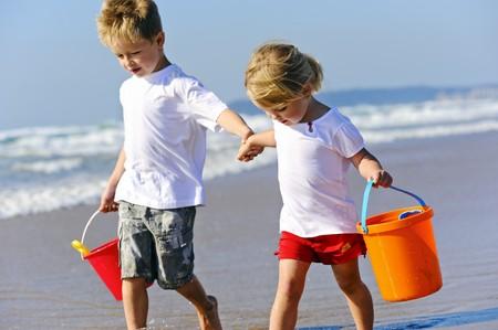 klein meisje op strand: Broer en zus lopen langs de rand van de oceaan op zoek naar schelpen