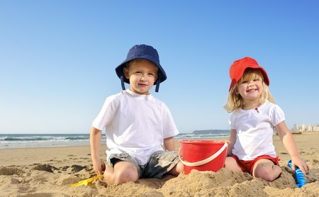 Gorgeous brother and sister ages 4 and 2 have fun digging in the sand at the beach Stock Photo - 7785540