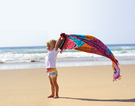 Young cute blonde child on vacation is holding a sarong in the wind Stock Photo - 7785551