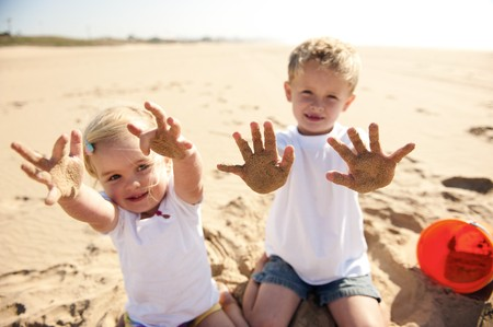 Kids on the beach show their sand covered hands to the camera photo
