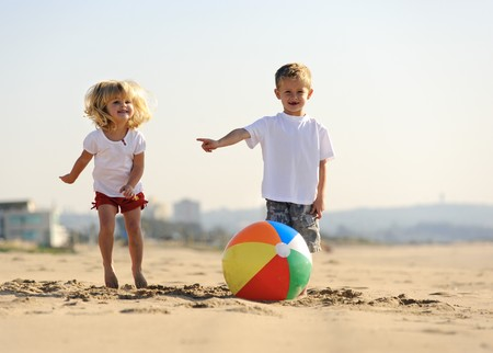 beach ball girl: Beautiful brother and sister play with a beach ball outdoors