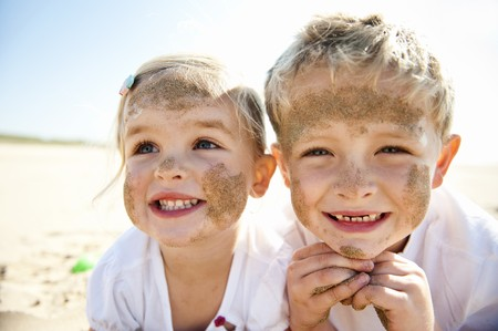 Brother and sister smile at the camera, brightly lit, on the beach, faces covered in sand. photo