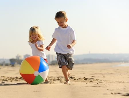 kids playing beach: Beautiful brother and sister play with a beach ball outdoors