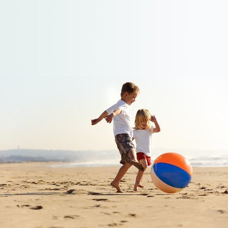 Beautiful brother and sister play with a beach ball outdoors photo