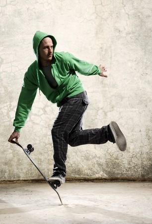 truc: Geschoolde skateboarder doet een truc voor grunge muur