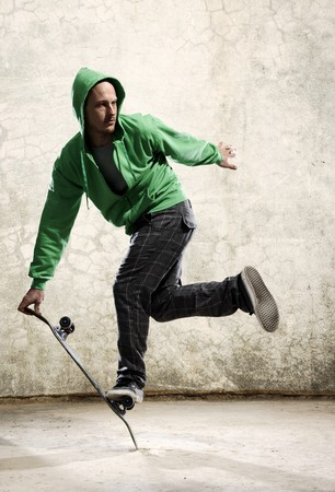trick: Skilled skateboarder does a trick in front of grunge wall Stock Photo