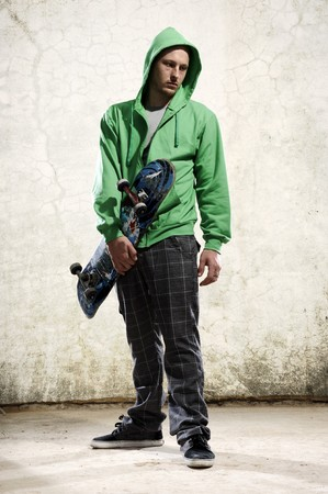 tough: Youth stands with skateboard and green hoodie Stock Photo