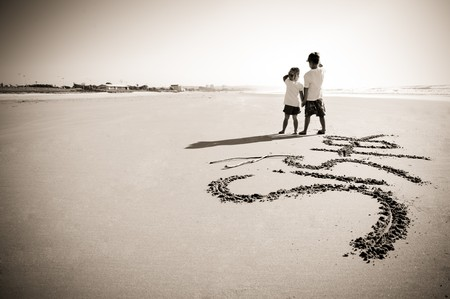 Lovely young brother and sister write words in the sand together Stock Photo - 7795877