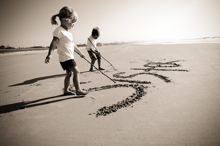 Lovely young brother and sister write words in the sand together Stock Photo - 7795876