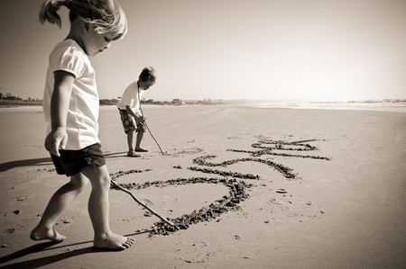 Lovely young brother and sister write words in the sand together Stock Photo - 7795878