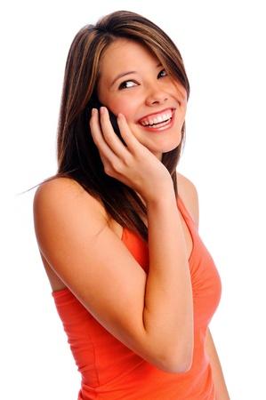 hablando por telefono: Muchacha bonita mediante tel�fono celular sonr�e y mira sobre su hombro fuera del marco de Foto de archivo