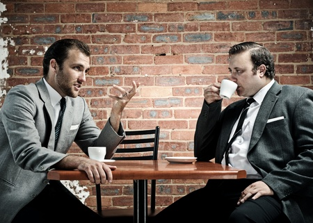 Coffee and conversation between two well dressed men photo