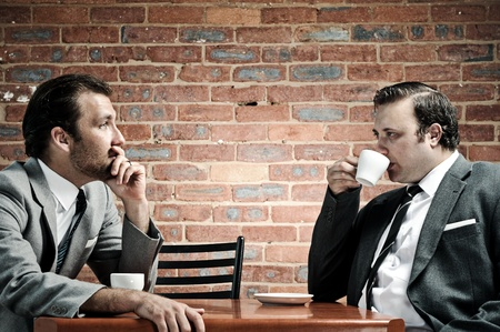 Two well dressed men in suits have coffee together, dramatic lighting photo