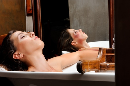 Woman relaxing in bathtub with mirror image of her with bruises on her face, a conceptual shoot of domestic abuse often hidden from public Stock Photo - 8726640