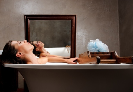 Woman relaxing in bathtub with mirror image of her with bruises on her face, a conceptual shoot of domestic abuse often hidden from public  photo