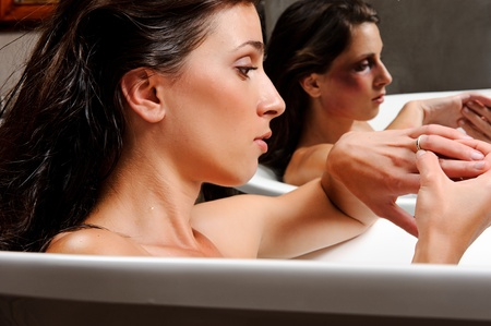 wife of bath: Woman relaxing in bathtub with mirror image of her with bruises on her face, a conceptual shoot of domestic abuse often hidden from public
