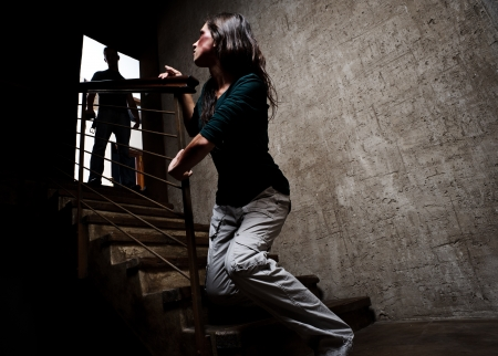 Concept of domestic abuse. Battered woman escaping from man silhouetted at the top of the stairs, in fear of more violence Stock Photo - 8726481