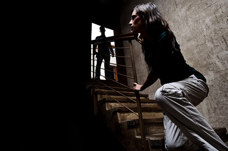 mujer golpeada: Concepto de abuso dom�stico. Mujer maltratada escapar del hombre que se perfilan en la parte superior de las escaleras, con el temor de m�s violencia