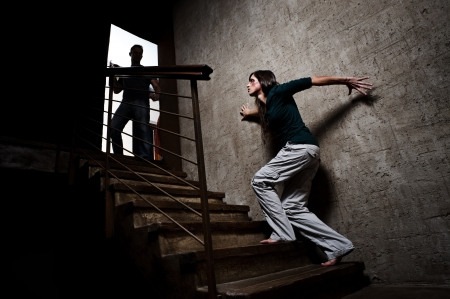 casualty: Concept of domestic abuse. Battered woman escaping from man silhouetted at the top of the stairs, in fear of more violence
