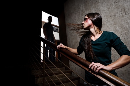 domination: Concept of domestic abuse. Battered woman escaping from man silhouetted at the top of the stairs, in fear of more violence