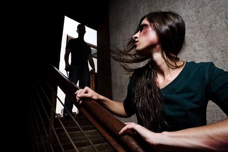 violencia: Concepto de abuso dom�stico. Mujer maltratada escapar del hombre que se perfilan en la parte superior de las escaleras, con el temor de m�s violencia