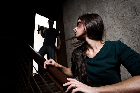 domestic abuse: Concept of domestic abuse. Battered woman escaping from man silhouetted at the top of the stairs, in fear of more violence