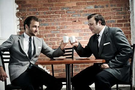 businessmen agree as the cheers with their coffee mugs photo