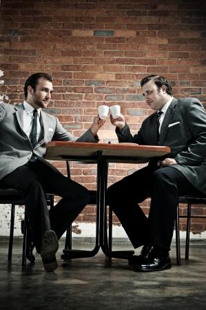 akkoord: Zakelijke deal in een cafe, overeengekomen met cappucinos  Stockfoto