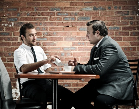 discussion in a coffee shop by two vintage businessmen photo