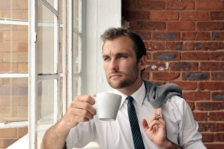 young man stares out the window while holding a coffee cup photo