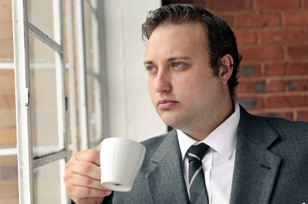 Old style man with coffee at the window while wearing suit photo