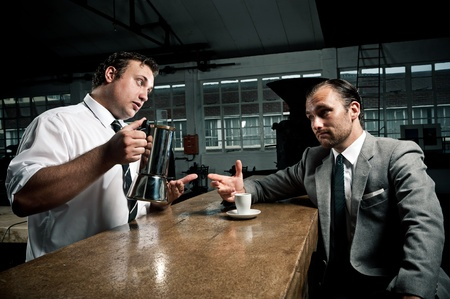 bar counters: Waitor offers man a refill of fresh coffee from the pot Stock Photo