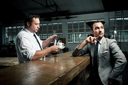 barista: Businessman ponders as barista tops up his coffee mug Stock Photo