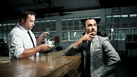 Businessman ponders as barista tops up his coffee mug photo