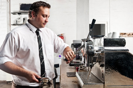 makes: professional expert barista makes coffee with a machine