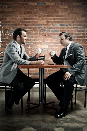 Two friends discuss the taste of coffee while wearing suits photo