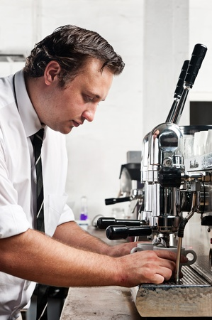 making coffee: professional expert barista makes coffee with a machine
