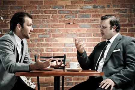 Animated debate between two vintage coffee connoisseurs Imagens