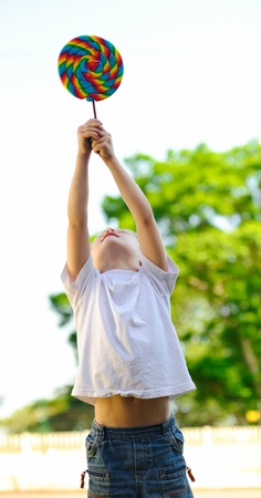 Young boy holds his lollipop high above his head photo